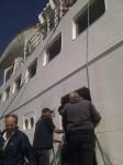 Umstieg in das Beiboot, rechts die Schiffswand des großen Schiffs