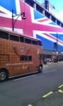 Bus in front behind big britishflag like house wall